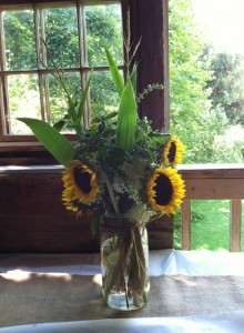 sunflowers in jar on table in rustic barn combsberry inn md