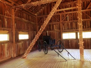 buggy parked in rustic barn with white lights strung around poles