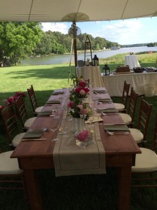 table decorated for wedding reception in outside tent by water oxford md