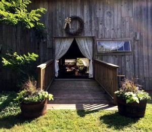 white lace curtains on barn door entrance into wedding reception