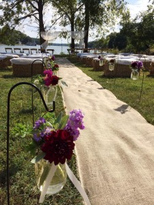 mason jars of flowers and seating set up for outdoor wedding