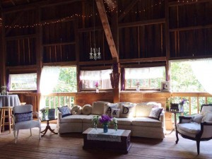 inside of barn couches and area decorated for wedding reception