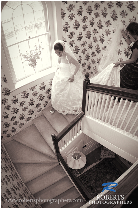 black and white photo of bride walking down stairway at combsberry inn