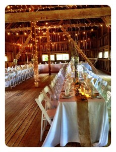tables all set for wedding reception with white lights lit up around poles in barn