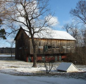 snow covered ground and rustic barn with snow on roof combsberry inn