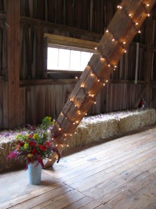 christmas lights on beam in barn with hay and flower petals