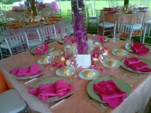 wedding reception tables set with pink napkins place settings and candles