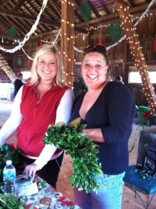 two women smiling holding decorations for barn wedding ceremony
