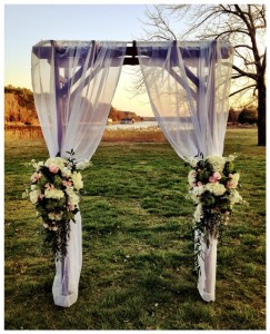 decorated alter with flowers and sheer curtains by oxford river