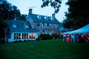 combsberry main house lit up at dusk with wedding guests under tent in lawn