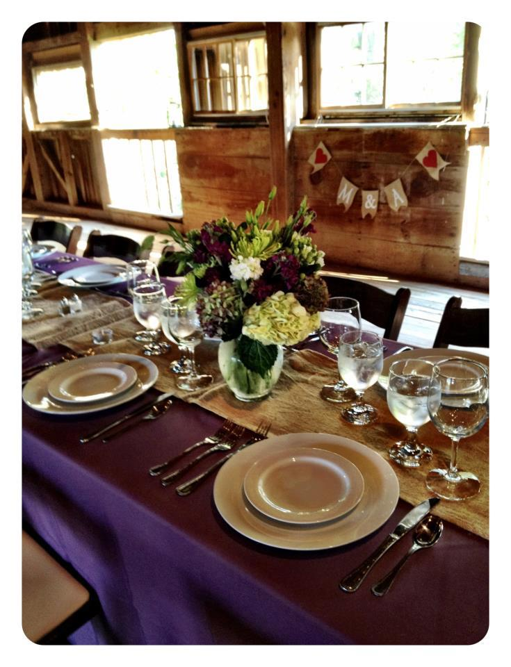 long table with purple tablecloth set for wedding reception