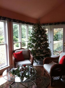 christmas tree in corner of room by chairs and glass table with christmas decorations