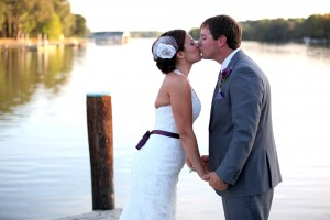 couple kissing facing each other holding hands on pier at combsberry inn