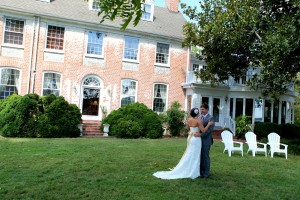 bride and groom facing each other in front of main house combsberry inn