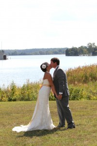 wedding couple kissing on lawn by water at combsberry inn