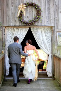 wedding couple walking into barn husband holding brides dress