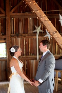 wedding couple standing in barn holding hands smiling