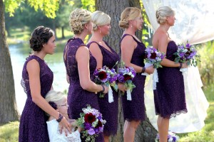 bridesmaids wearing purple dresses standing during ceremony