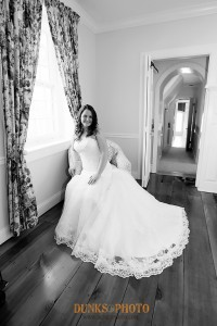black and white photo of bride sitting in chair by window