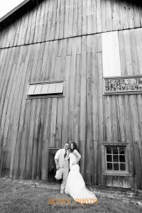 married couple posed in front of barn in black and white photo