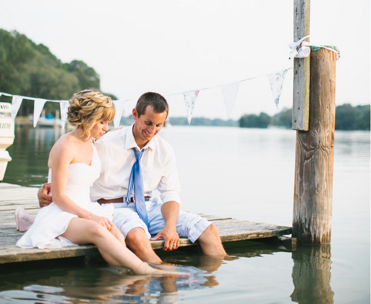 just married couple sitting on pier with feet in water looking down