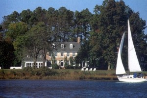 view of combsberry inn from oxford river with sailboat going by