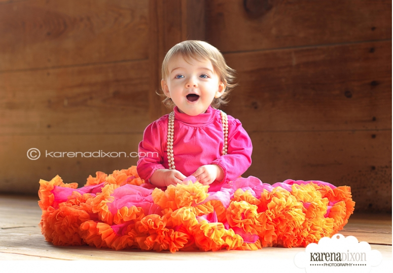 little girl dressed in fluffy skirt sitting in barn for photo shoot