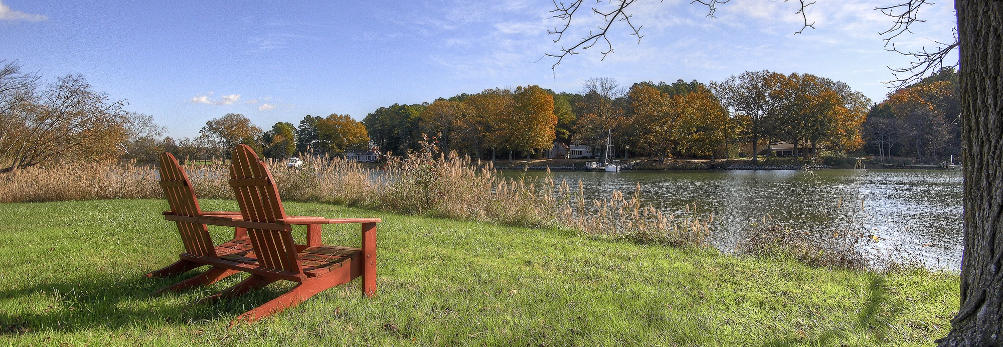 two red adirondacks in grass waterside with trees in background