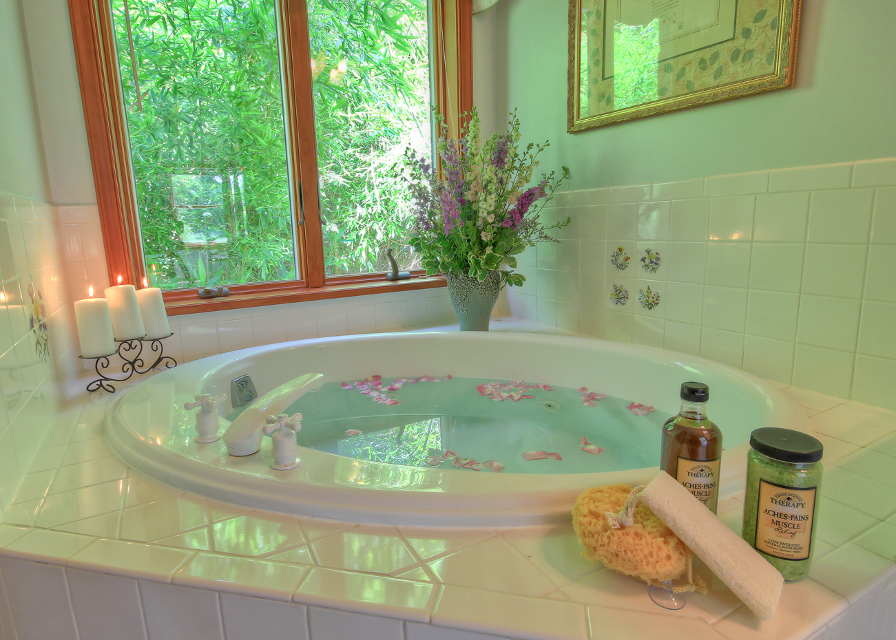 corner jacuzzi tub with drawn bath and rose petals and candles lit