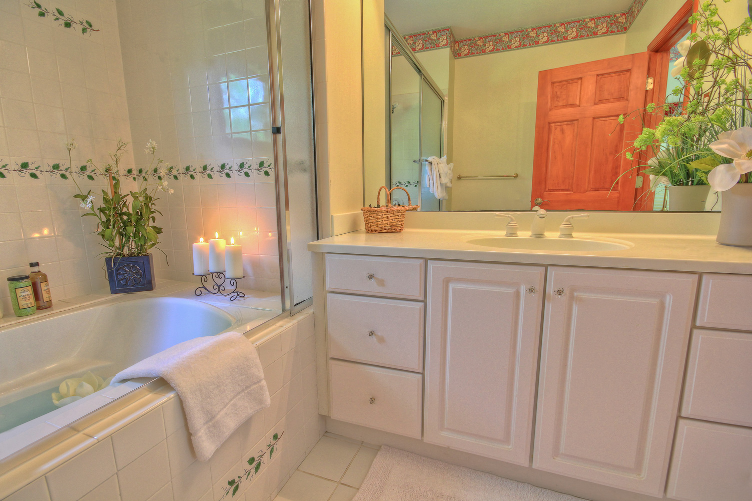 drawn tub with lit candles and vanity area in bathroom combsberry inn