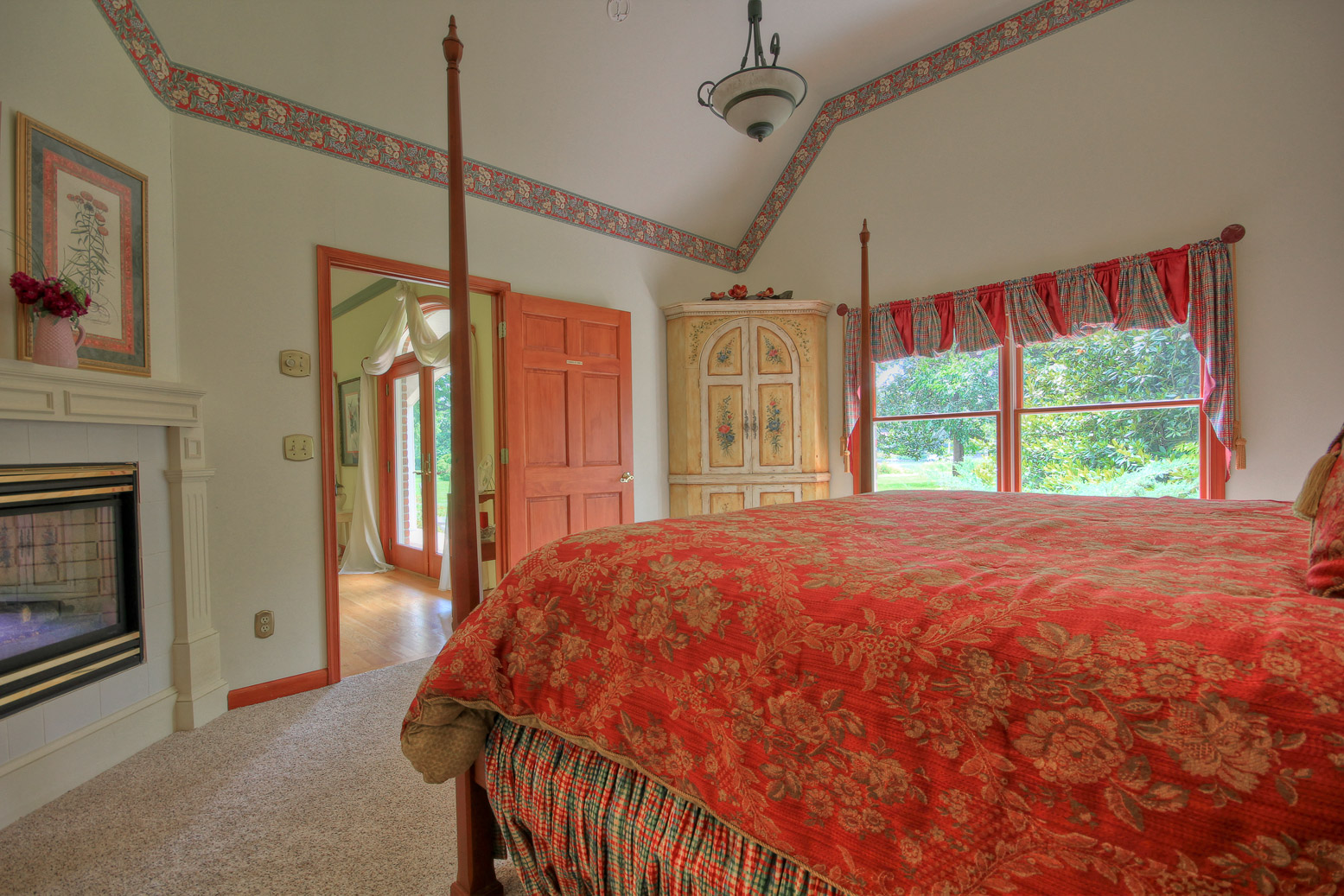 view of eden room from beside bed with fireplace and dresser
