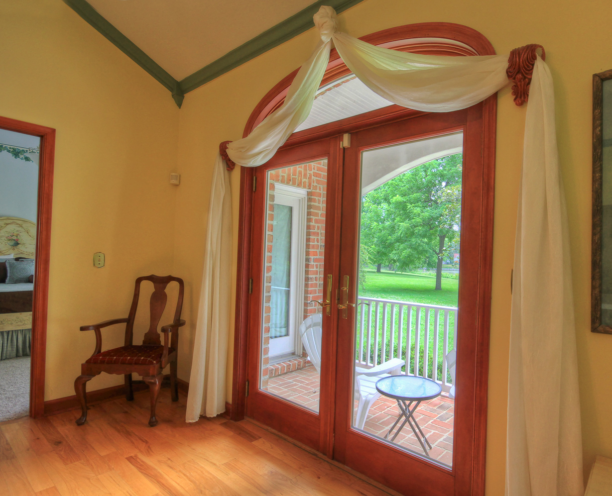 french doors leading to back porch and chair in corner at combsberry inn main house