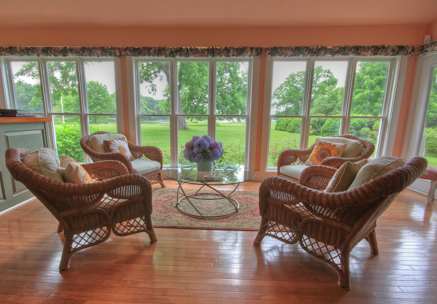 four wicker chairs around glass table with view of water off in distance