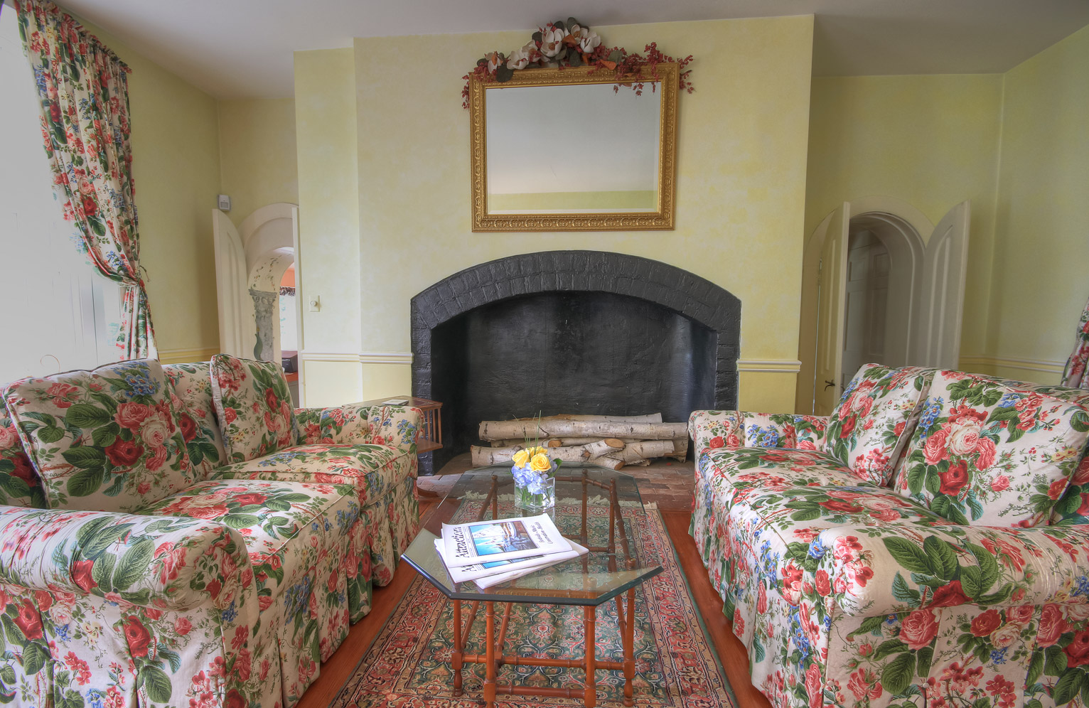 two couches and table in middle in front of fireplace in main sitting room combsberry inn