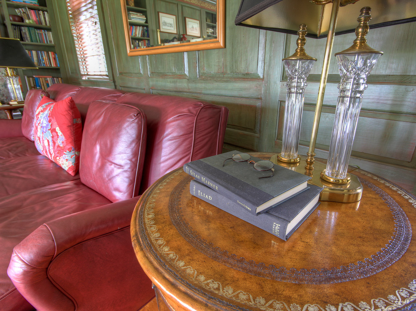 red leather sofa in combsberry library next to table with books and glasses