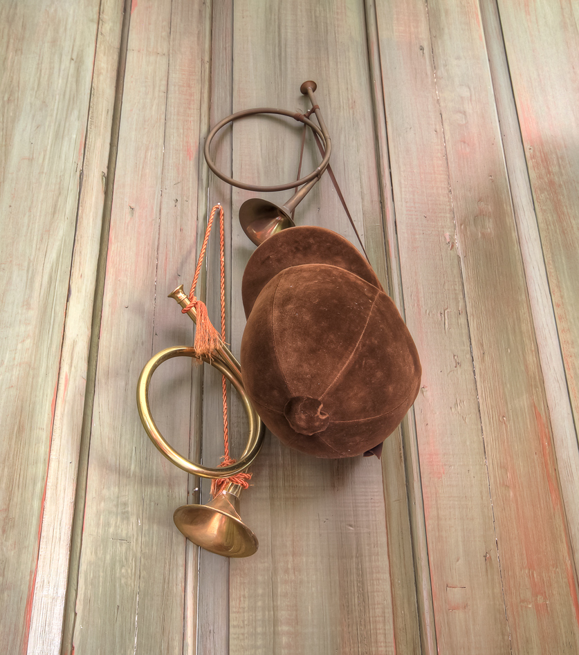 two horn instruments hanging on wall with brown hat