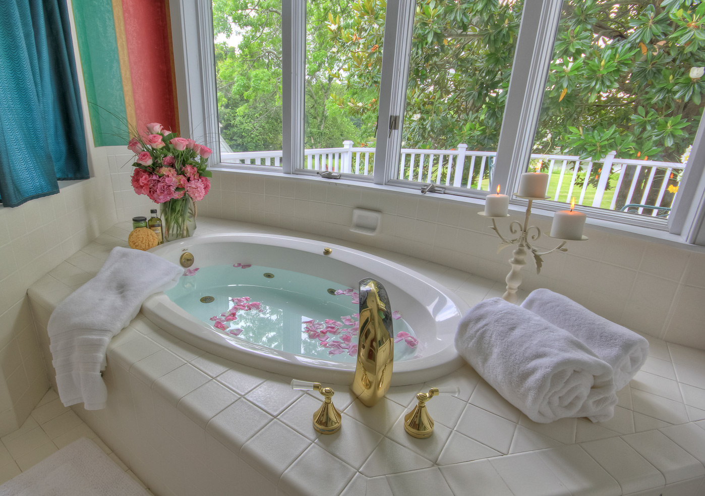 jacuzzi tub by window at combsberry inn with drawn bath and rose petals