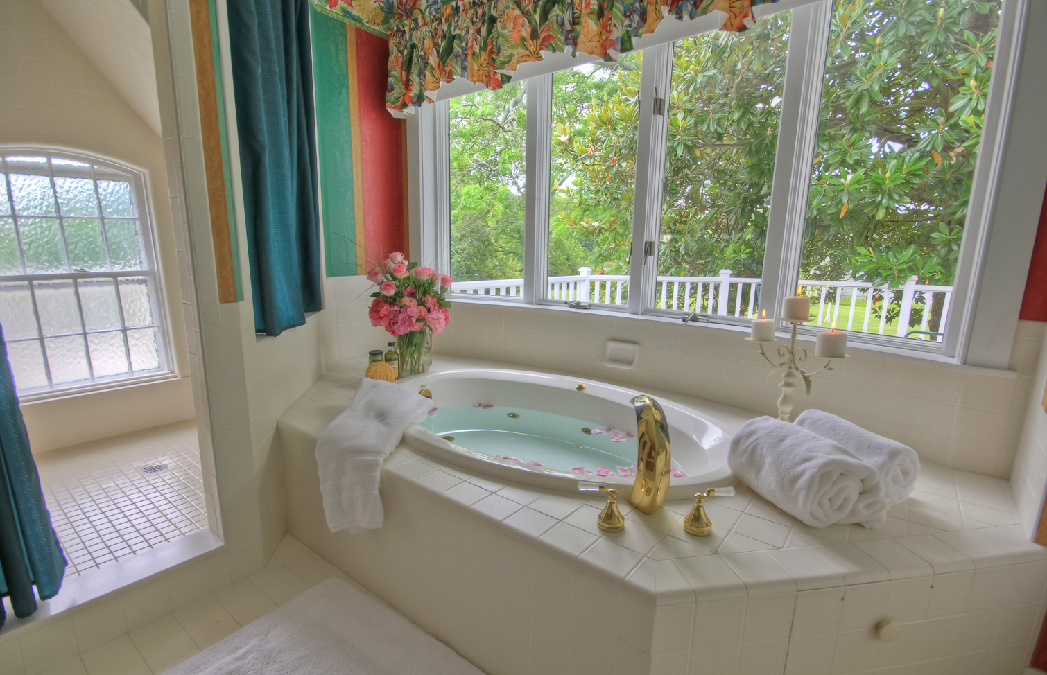 drawn bath with rose petals flower arrangement and lit candles by large windows
