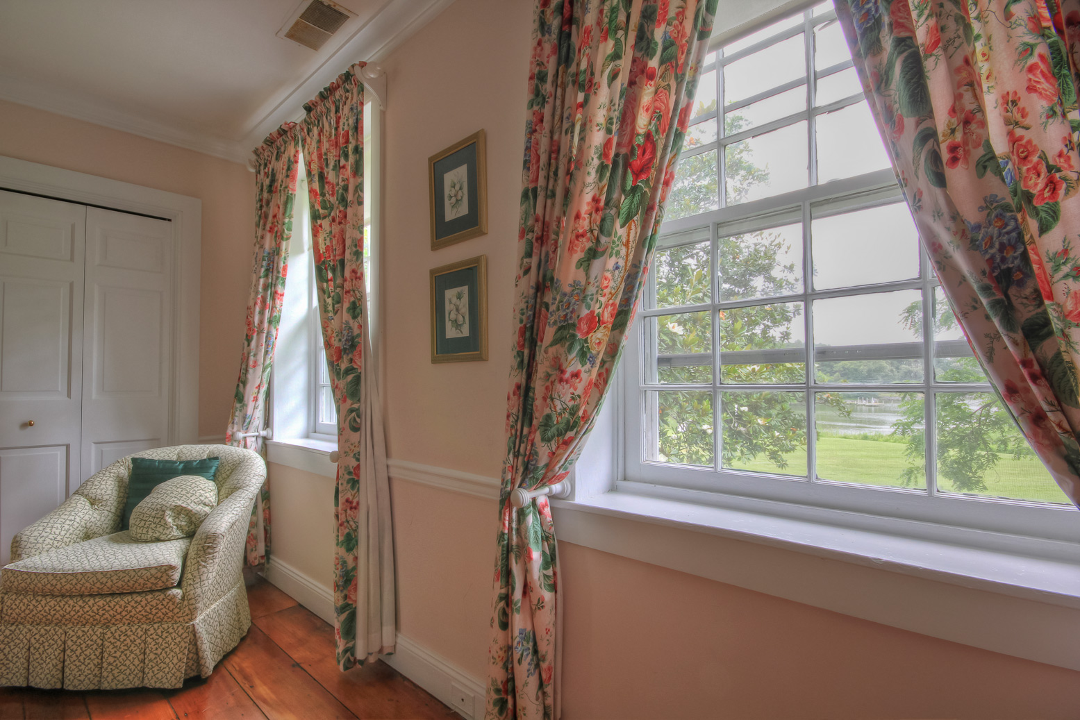 two windows with flower drapes and chair in corner in magnolia suite combsberry inn