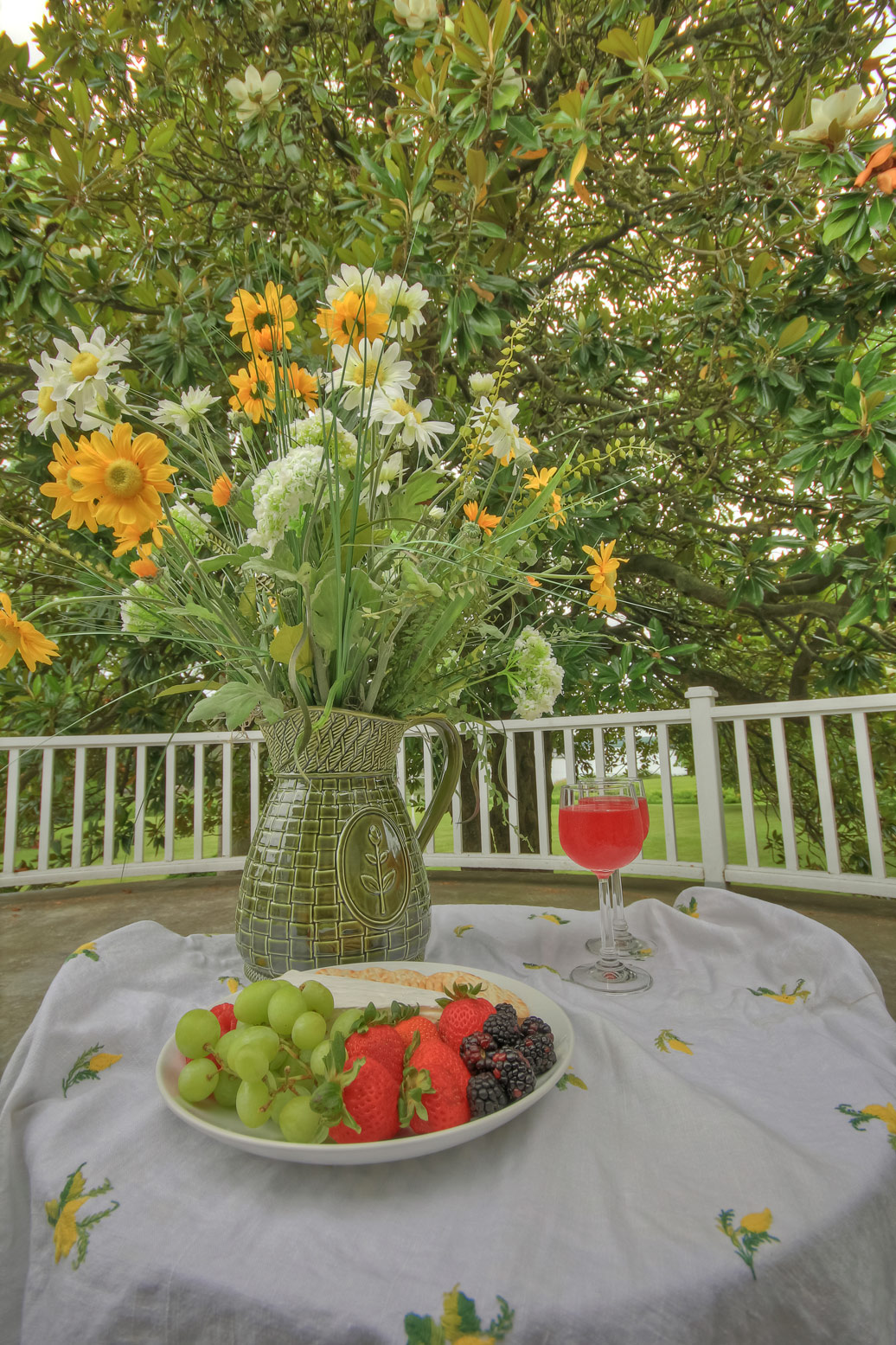 cheese plate with fruit wine glasses and flower arrangement on outside table on patio