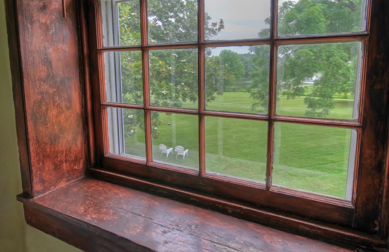 view looking out from window in combsberry inn of yard and adirondack chairs