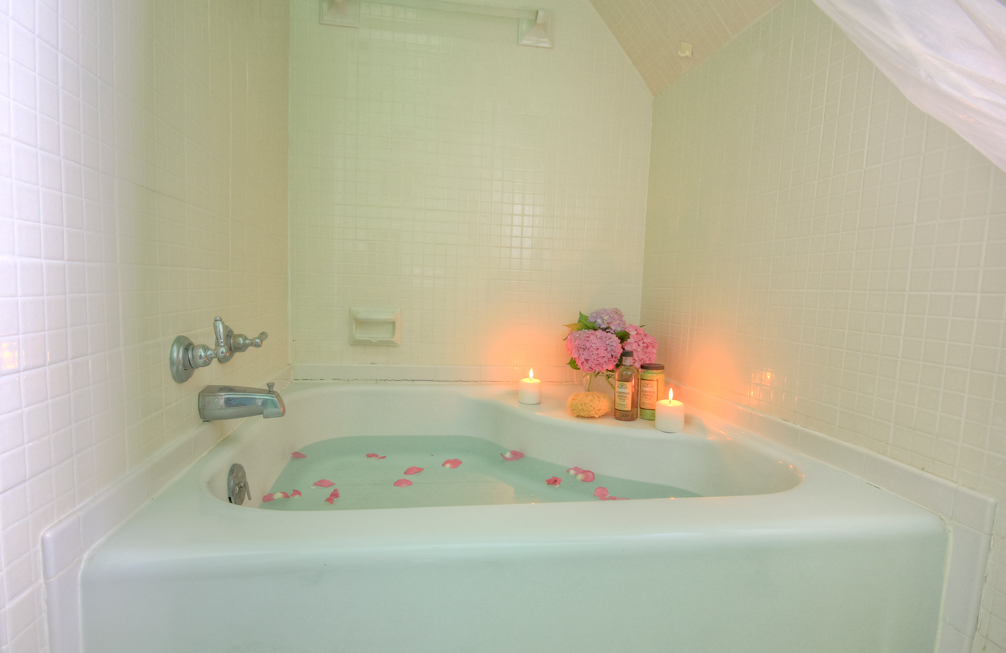 drawn bath in heart shaped tub with rose petals and lit candles