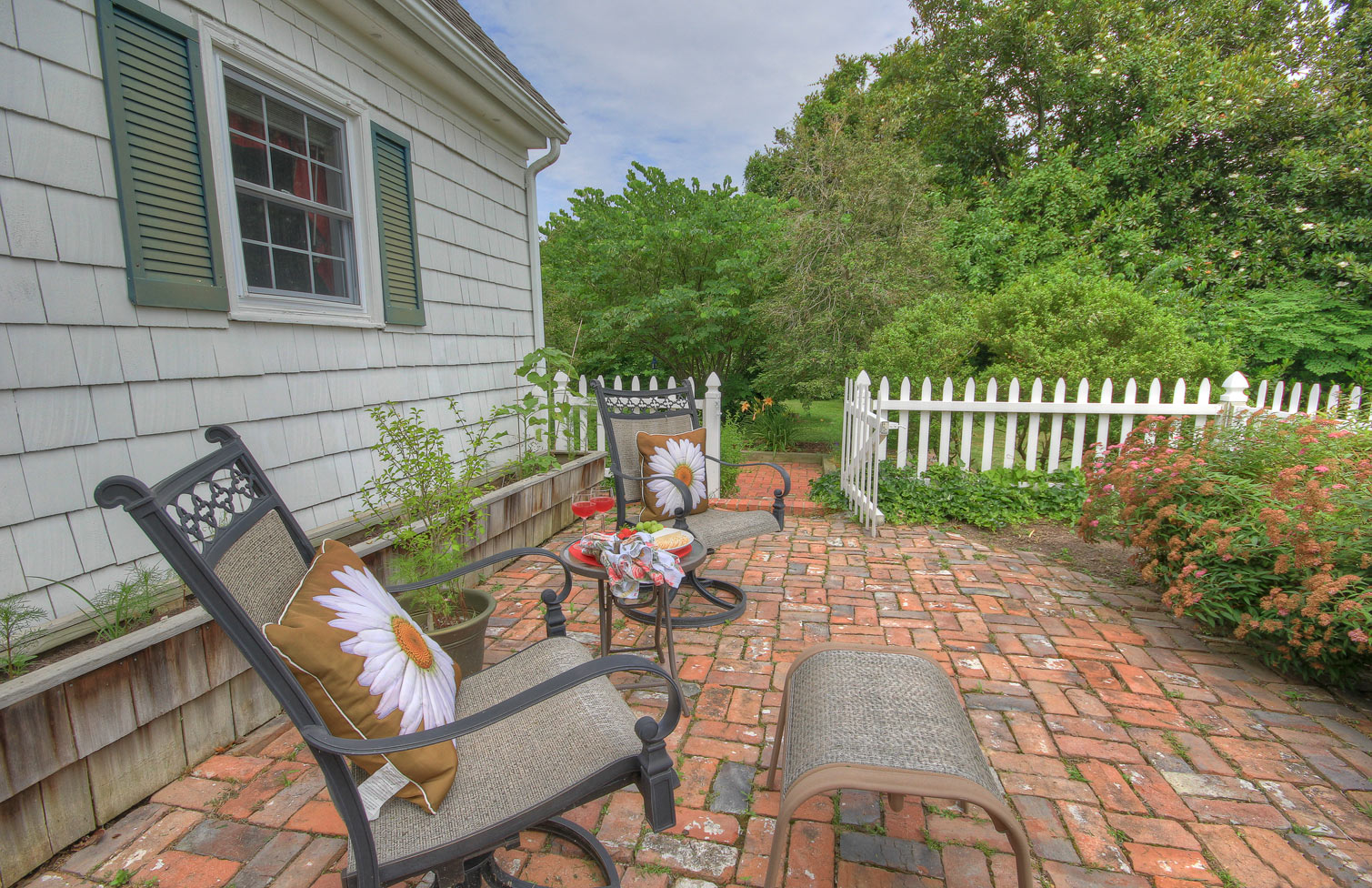 brick cottage deck at oxford cottage with two rockers table and table