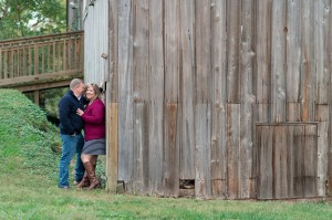 couple engaged leaning against rustic barn oxford md