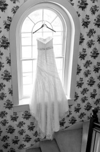 bridal gown hanging in window for photo shoot combsberry inn