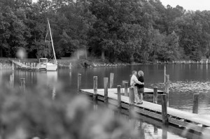 black and white photo of couple hugging on pier oxford river md