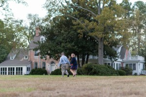 happy couple walking through combsberry lawn holding hands