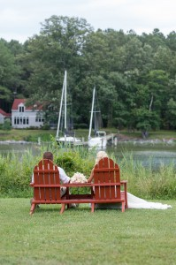 bride and groom sitting back to in adirondack chairs by oxford river