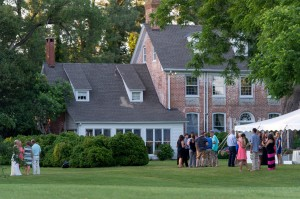 wedding guests standing on lawn in front of combsberry inn