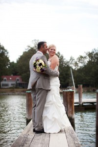 bride and groom hugging for photo on pier of oxford river